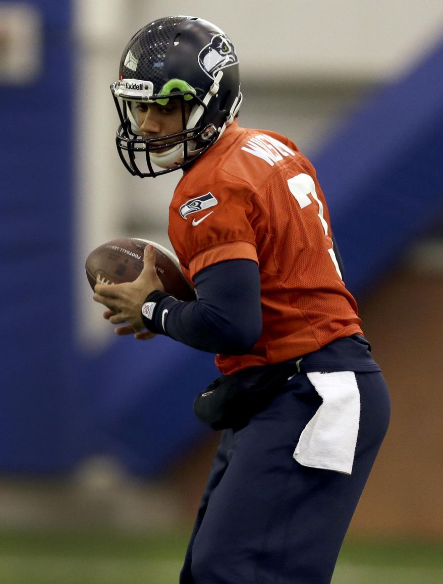 Seattle Seahawks quarterback Russell Wilson handles a ball during NFL football practice Thursday, Jan. 30, 2014, in East Rutherford, N.J. The Seahawks and the Denver Broncos are scheduled to play in the Super Bowl XLVIII football game Sunday, Feb. 2, 2014. (AP Photo)