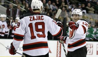 New Jersey Devils' Travis Zajac (19) is congratulated by teammate Damien Brunner (12), of Switzerland, after scoring in the second period of an NHL hockey game against the Dallas Stars, Thursday, Jan. 30, 2014, in Dallas. (AP Photo/Tony Gutierrez)