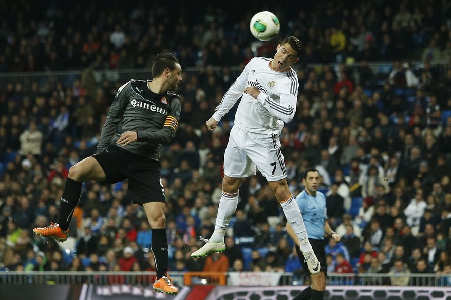 Real Madrid's Cristiano Ronaldol, right, in action with Espanyol's Sergio Garcia, left, during a Copa del Rey soccer match between Real Madrid and Espanyol at the Santiago Bernabeu stadium in Madrid, Spain, Tuesday, Jan. 28, 2014. (AP Photo/Andres Kudacki)