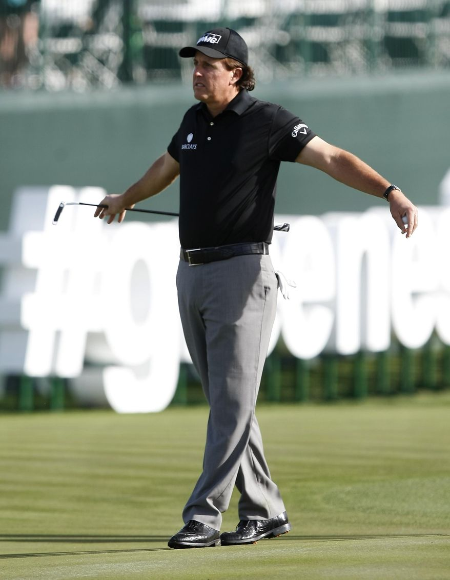 Phil Mickelson stretches on the 17th hole during the first round of the Waste Management Phoenix Open golf tournament on Thursday, Jan. 30, 2014, in Scottsdale, Ariz. (AP Photo/Rick Scuteri)