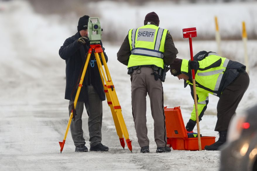 Officers from the St. Clair County Sheriff's Department investigate a scene where bags of human remains were discovered Thursday, Jan. 30, 2014 at the intersection Allington and Fred Moore Highway in St. Clair Township. Police are searching for a middle-aged white woman driving a late 90's gray or tan sport utility vehicle. (AP PHOTO/TIMES HERALD, JEFFREY SMITH)