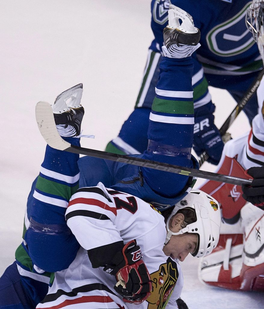 Vancouver Canucks left wing Daniel Sedin (22) goes head over heels over Chicago Blackhawks defenceman Sheldon Brookbank (17) during the second period of NHL action in Vancouver, British Columbia Wednesday, Jan. 29, 2014. (AP Photo/The Canadian Press, Jonathan Hayward)