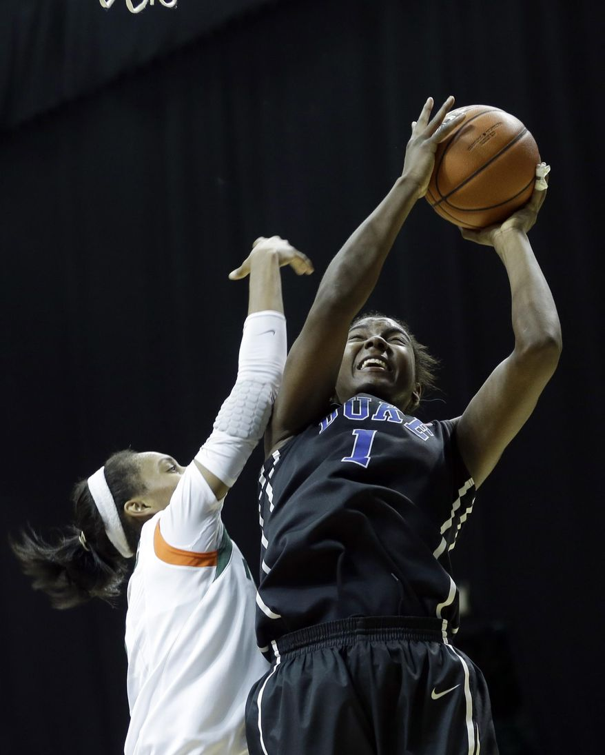 Duke Blue Devils forward/center Elizabeth Williams (1) prepares to shoot as Miami Hurricanes guard Caprice Dennis (1) defends  during the second half of an NCAA college basketball game in Coral Gables, Fla., Thursday, Jan. 30, 2014. Duke won 76-75. (AP Photo)