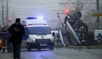 FILE - In this Monday, Dec. 30, 2013 file photo an ambulance leaves the site of an explosion after a bomb blast tore through a trolleybus, background, in the city of Volgograd. Russia's counter terrorism agency on Thursday, Jan. 30, 2014, identified the two suicide bombers who struck the southern city of Volgograd and announced the arrest of two suspected accomplices. The bombings of a train station and trolley bus in Volgograd in late December, which killed 34 people and wounded many more, heightened security fears before the Winter Olympics in Sochi, which start next week.  (AP Photo/Denis Tyrin, File)
