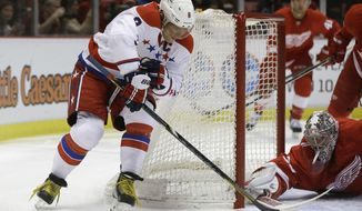 Detroit Red Wings goalie Jimmy Howard (35) stops a wrap-around attempt by Washington Capitals right wing Alex Ovechkin (8) during the first period of an NHL hockey game in Detroit, Friday, Jan. 31, 2014. (AP Photo/Carlos Osorio)