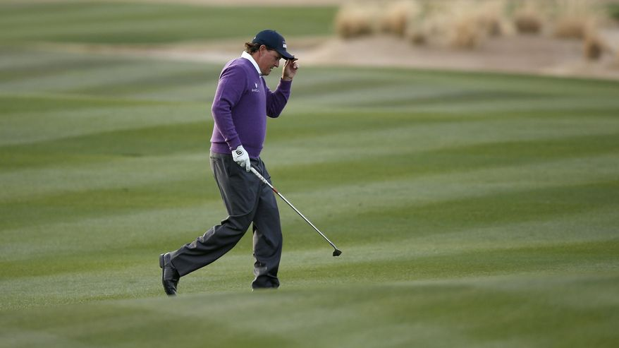 Phil Mickelson tips his cap to the crowd after hitting a chip shot onto the green at the 17th hole during the second round of the Phoenix Open golf tournament on Friday, Jan. 31, 2014, in Scottsdale, Ariz. (AP Photo/Ross D. Franklin)