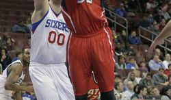 Atlanta Hawks' Mike Scott (32) shoots as Philadelphia 76ers' Spencer Hawes (00) defends in the second half of an NBA basketball game, Friday, Jan. 31, 2014, in Philadelphia. The Hawks won 125-99. (AP Photo/H. Rumph Jr.)