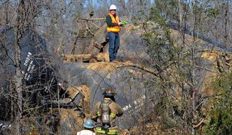 Emergency crews work the scene of a Canadian National Railway train derailment along U.S. 98, West of New Augusta Miss., on Friday, Jan. 31, 2014. A train derailment Friday in southeast Mississippi sparked a small evacuation and highway closure after rail cars began leaking fuel oil.  (AP Photo/Hattiesburg American, Ryan Moore) NO SALES