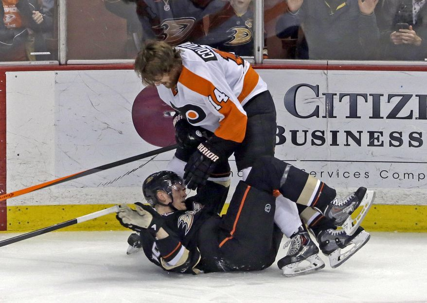Philadelphia Flyers center Sean Couturier (14) loses his helmet as he and Anaheim Ducks right winger Corey Perry (10) tussle in the second period of an NHL hockey game in Anaheim, Calif., Thursday, Jan. 30, 2014. (AP Photo)