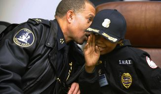 Detroit Police Chief James Craig whispers in the ear of Jayvon Felton, 9, after Felton was named Chief for A Day by Craig, at Detroit Public Safety Headquarters in Detroit on Friday Jan. 31, 2014. Felton, 9, was diagnosed with acute lymphoblastic leukemia in April.   (AP Photo/Detroit News, David Coates)  DETROIT FREE PRESS OUT; HUFFINGTON POST OUT