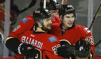 Calgary Flames' Sean Monahan, right, celebrates his goal with teammate TJ Galiardi during third period NHL hockey action against the San Jose Sharks in Calgary, Canada, Thursday, Jan. 30, 2014. The Flames defeated the Sharks 4-1. (AP Photo/The Canadian Press, Jeff McIntosh)