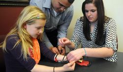 FOR RELEASE MONDAY, FEB. 3, 2014, AT 12:01 A.M. CST. - In this photo from Jan. 16, 2014, from left, West Texas A&M students Alex Parra and Rikki Boelens help Aly Hunt, 10, with her hand prosthesis in Canyon, Texas. Four West Texas A&M University students worked on an affordable mechanical hand design for Texas Scottish Rite Hospital for Children in Dallas. (AP Photo/The Amarillo Globe News, Sean Steffen)