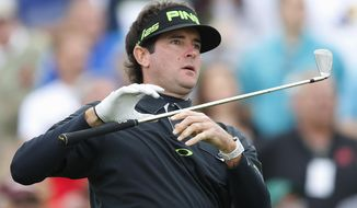 Bubba Watson lets go of his iron as he watches his tee shot on the seventh hole during the second round of the Phoenix Open golf tournament on Friday, Jan. 31, 2014, in Scottsdale, Ariz. (AP Photo/Ross D. Franklin)