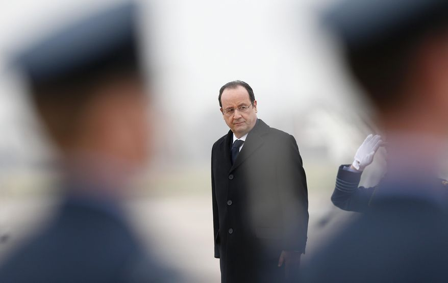 French President Francois Hollande listens to the French National Anthem before reviewing an honour guard, after his arrival for a one-day summit with Britain's Prime Minister David Cameron, not pictured, at the RAF Brize Norton airbase in Brize Norton, England, Friday, Jan. 31, 2014.  (AP Photo/Andrew Winning, Pool)