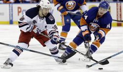 New York Rangers' Mats Zuccarello (36) and New York Islanders' Thomas Hickey (14) fight for control of the puck during the second period of an NHL hockey game on Friday, Jan. 31, 2014, in New York. (AP Photo/Frank Franklin II)