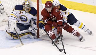 Phoenix Coyotes' Tim Kennedy (34) tries to get off a shot as Buffalo Sabres' Steve Ott (9) defends as Sabres goalie Ryan Miller (30) watches the puck during the third period of an NHL hockey game Thursday, Jan. 30, 2014, in Glendale, Ariz.  The Sabres defeated the Coyotes 3-2. (AP Photo)