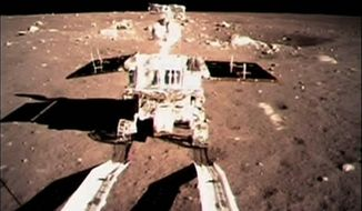 """FILE - In this Dec. 15, 2013 file photo taken by the on-board camera of the lunar probe Chang'e-3 and made off the screen of the Beijing Aerospace Control Center in Beijing, China's first moon rover """"Jade Rabbit"""" touches the lunar surface. Fans of China's Jade Rabbit moon rover sent Lunar New Year greetings to the robot Friday, Jan. 31, 2014, wishing it a speedy recovery from a malfunction it reported in a melodramatic dispatch by an official news agency before going into hibernation. (AP Photo/Xinhua, File) NO SALES"""