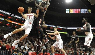 Louisville's Luke Hancock, left, passes as Cincinnati's Justin Jackson defends during the second half of an NCAA college basketball game Thursday, Jan. 30, 2014, in Louisville, Ky. Cincinnati defeated Louisville 69-66. (AP Photo/Timothy D. Easley)
