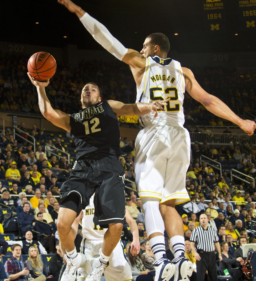 Purdue guard Bryson Scott (12) tries to make a basket while defended by Michigan forward Jordan Morgan (52) in the second half of an NCAA college basketball game in Ann Arbor, Mich., Thursday, Jan. 30, 2014. Michigan won 75-66. (AP Photo/Tony Ding)