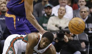 Milwaukee Bucks' Brandon Knight, bottom, and Phoenix Suns' Channing Frye watch a loose ball during the first half of an NBA basketball game Wednesday, Jan. 29, 2014, in Milwaukee. (AP Photo/Jeffrey Phelps)