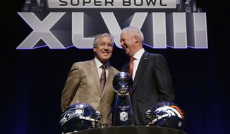 Seattle Seahawks head coach Pete Carroll, left, and Denver Broncos head coach John Fox laugh as they pose behind the Vince Lombardi Trophy before speaking at a news conference Friday, Jan. 31, 2014, in New York. The Seahawks and the Broncos are scheduled to play in the NFL Super Bowl XLVIII football game on Sunday, Feb. 2, at MetLife Stadium in East Rutherford, N.J. (AP Photo/Matt Slocum)