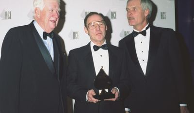 """FILE - In a Jan. 14, 1990 file photo, Burt Reinhardt, center, President of the Cable News Network, (CNN), holds his Golden Ace Award for the network's coverage of the Beijing uprisings at the Eleventh Annual Award for Cable Excellence in Los Angeles. Standing at right is Ted Turner, owner of CNN and former Speaker of the House Thomas """"Tip"""" O'Neil. Reinhardt, one of CNN's first presidents and a television pioneer who is credited with helping to build the global news network in its formative years, died at his home near Atlanta on Tuesday. He was 91. Reinhardt joined CNN in 1979 as the start-up network prepared to launch, his daughter said. Turner Broadcasting founder Ted Turner named Reinhardt as president in January 1982. (AP Photo/Alan Greth, File)"""