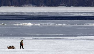Mike Fortier walks off Lake Winnipesaukee Friday, Jan. 31, 2014 by a section of thin ice and open water in a section of the lake called the Broads in Gilford, N.H. As thousands of winter sports enthusiasts take to the lakes this weekend, a warning by the state Fish and Game department says that despite a cold winter that ice levels on the lakes are unpredictable. (AP Photo/Jim Cole)
