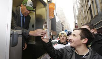 "New York Jets head coach Rex Ryan, left, hands out free ice cream from a truck Friday, Jan. 31, 2014 on Broadway in New York. Ryan was taking part in an ""Embrace the Cold"" promotion by the New Era Cap Company to promote their Super Bowl merchandise. The Seattle Seahawks will play the Broncos Sunday in the NFL Super Bowl XLVIII football game in East Rutherford, N.J. (AP Photo/Ted S. Warren)"