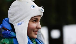 A volunteer wearing a hat with one of the Olympic mascots smiles in the ski resort Rosa Khutor in Krasnaya Polyana, Russia, Friday, Jan. 31, 2014. The snow and sliding sports venues for the Sochi 2014 Winter Olympics are located in Krasnaya Polyana. (AP Photo/Gero Breloer)