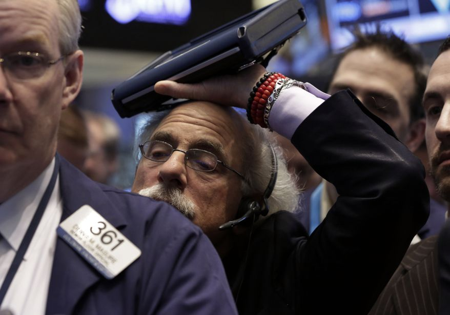 Trader Peter Tuchman rests his handheld device on his head as he works on the floor of the New York Stock Exchange Friday, Jan. 31, 2014. Stocks fell sharply in early trading Friday, as investors fretted over disappointing earnings from companies like Amazon.com and more trouble in overseas markets. (AP Photo/Richard Drew)