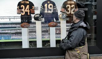 Football fan Brian Jackson, of Newark, N.J. stops to look at autographed memorabilia of NFL Hall of Fame players, Walter Payton, Johnny Unitas, and Jim Brown at a store along Super Bowl Boulevard Friday, Jan. 31, 2014, in New York. The Denver Broncos take on the Seattle Seahawks in Super Bowl XLVIII Sunday at Metlife Stadium in East Rutherford, N.J. (AP Photo/Chris O'Meara)