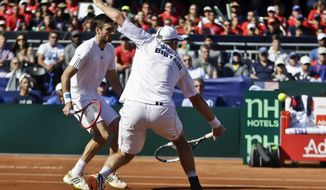 Britain's Dominic Inglot returns a shot from the United State team as his teammate Colin Fleming looks on during a doubles match at the Davis Cup tennis matches, Saturday Feb. 1, 2014, in San Diego. (AP Photo/Lenny Ignelzi)