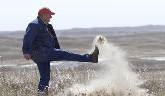 FILE - In this Sept. 29, 2014 file photo Atkinson, Neb., rancher Bruce Boettcher, who opposes the Keystone XL pipeline, kicks up sand on his land, to demonstrate the fragility of the sand hills near the planned route of the pipeline. The long-delayed Keystone XL oil pipeline cleared a major hurdle Friday, Jan. 31, 2015 as the U.S.State Department raised no major environmental objections to the controversial pipeline from Canada through the heart of the U.S. Republicans and some oil- and gas-producing states cheered, but the report further rankled environmentalists already at odds with President Barack Obama. (AP Photo/Nati Harnik, File)