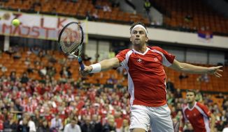 Switzerland's Michael Lammer, foreground returns a ball as his partner Marco Chiudinelli looks on,  during their Davis Cup World Group play-off first round doubles tennis match against Nenad Zimonjic and Filip Krajinovic of Serbia, in Novi Sad, Serbia, Saturday, Feb. 1, 2014. (AP Photo/Darko Vojinovic)