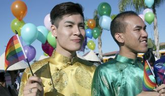 Timothy Truong, left, and Peterson Pham march with others Saturday Feb. 1, 2014 in the Lunar New Year parade, as part of the gay and lesbian group Viet Rainbow of Orange County, in Westminster, Calif. At least 70 people marched under the banner of the gay and lesbian group at the annual Tet parade in Little Saigon. About 12,000 spectators were expected to turn out for the parade. (AP Photo/Nick Ut)