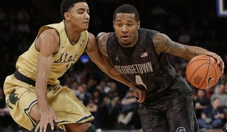 Michigan State's Gary Harris (14) defends Georgetown's D'Vauntes Smith-Rivera (4) during the first half of an NCAA college basketball game Saturday, Feb. 1, 2014, in New York. (AP Photo/Frank Franklin II)