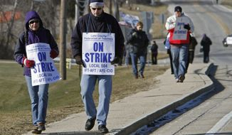 FILE - In this Jan. 12, 2012 file photo, teachers strike outside Zion-Benton High School in Zion, Ill., after negotiations between the teachers union and District 126 broke down. An education funding advisory committee is urging for the state's school funding formula to be changed to provide more equity to rich and poor districts across Illinois during tough economic times. Lawmakers, who will detail the proposal Monday, Feb. 3, 2014, aim to turn the report into legislation by the spring. (AP Photo/Daily Herald, Steve Lundy, File)