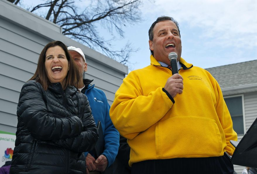 First lady Mary Pat Christie, left, laughs as New Jersey Gov. Chris Christie greet volunteers and family and neighbors outside a renovated home that was heavily damaged by Superstorm Sandy in a town near MetLife Stadium, where Sunday's Super Bowl game is to be played, Friday, Jan. 31, 2014, in Moonachie, N.J. The Christies moved some furniture to help a family move back into a home rebuilt after Superstorm Sandy. The volunteer event Friday was part of the NFL-sanctioned Rebuilding Together event. (AP Photo/Mel Evans)