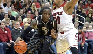 Central Florida's Isaiah Sykes, left, attempts to drive under the defense of Louisville's Wayne Blackshear during the first half of an NCAA college basketball game on Saturday, Feb. 1, 2014, in Louisville, Ky. (AP Photo/Timothy D. Easley)