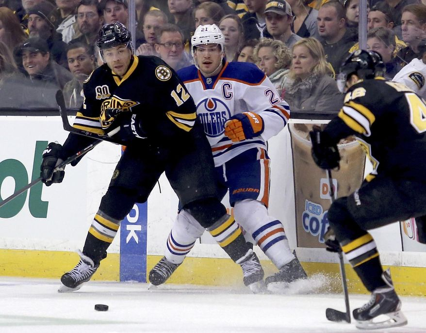 Edmonton Oilers defenseman Andrew Ference (21) is pushed against the boards as Boston Bruins right wing Jarome Iginla (12) passes the puck during the first period of an NHL hockey game, Saturday, Feb. 1, 2014 in Boston. (AP Photo/Mary Schwalm)