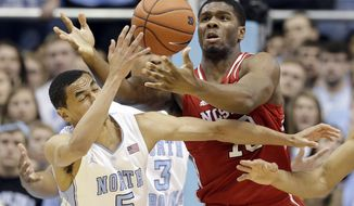 North Carolina's Marcus Paige (5) and North Carolina State's Lennard Freeman battle for a rebound during the first half of an NCAA college basketball game in Chapel Hill, N.C., Saturday, Feb. 1, 2014. (AP Photo/Gerry Broome)