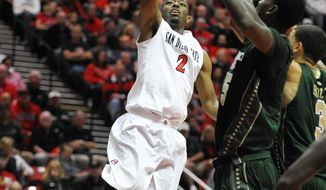 San Diego State's Xavier Thames (2) shoots over the defense of Colorado State's Gerson Santo (15) and Marcus Holt (3) during the first half of an NCAA college basketball game on Saturday, Feb. 1, 2014, in San Diego. (AP Photo/Denis Poroy)