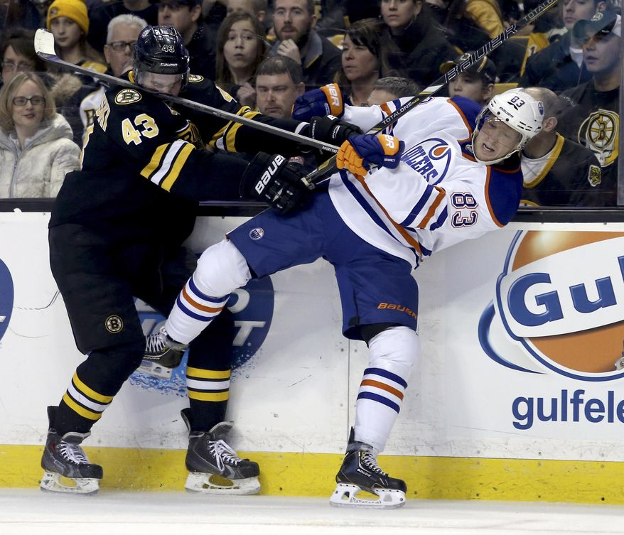 Boston Bruins defenseman Matt Bartkowski (43) takes a stick in the face as he checks Edmonton Oilers right wing Ales Hemsky (83), of the Czech Republic, into the boards during the second period of an NHL hockey game, Saturday, Feb. 1, 2014 in Boston. (AP Photo/Mary Schwalm)