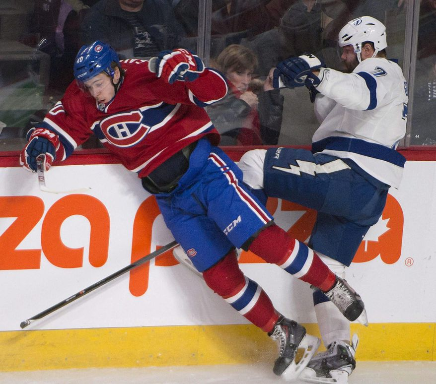 Montreal Canadiens Nathan Beaulieu and Tampa Bay Lightning Radko Gudas collide as they scramble for the puck during first period of an NHL game in Montreal Saturday, Feb. 1, 2014. (AP Photo/The Canadian Press, Peter McCabe)