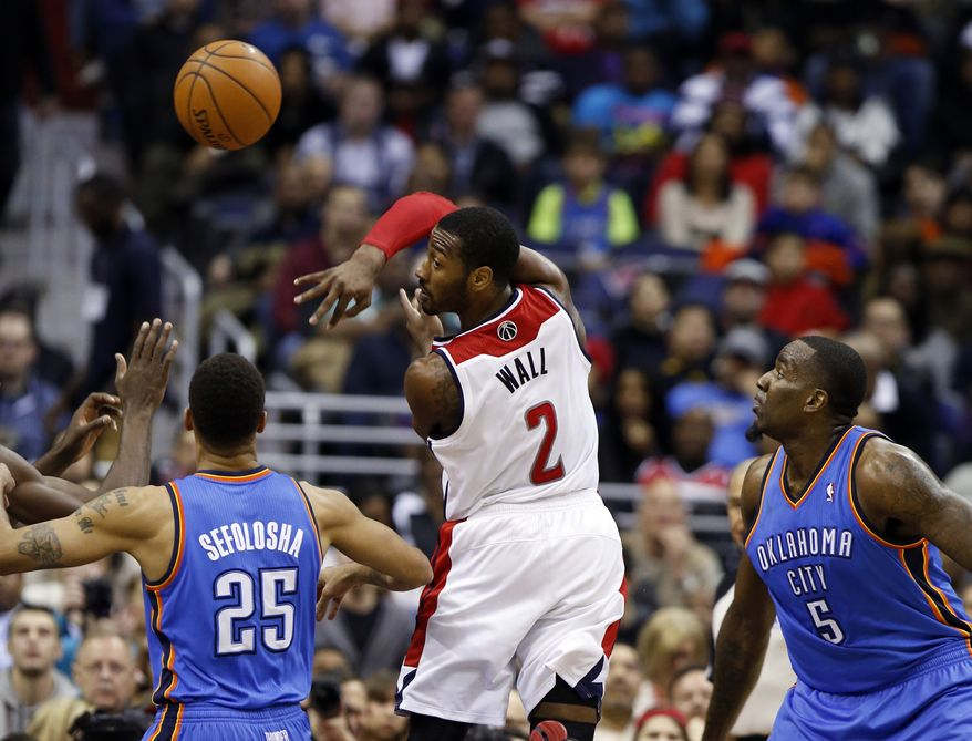 Washington Wizards guard John Wall (2) passes the ball over his shoulder past Oklahoma City Thunder guard Thabo Sefolosha (25), from Switzerland, and center Kendrick Perkins (5) in the first half of an NBA basketball game on Saturday, Feb. 1, 2014, in Washington. The Wizards won 96-81. (AP Photo/Alex Brandon)