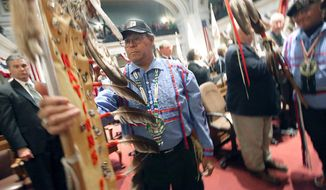 FILE - In this April 9, 2013 file photo, United States Army veteran and Forest County Potawatomi tribe member Jayson Jackson positions an eagle feather staff in the Assembly chambers of the Wisconsin State Capitol prior to the annual State of the Tribes address in Madison, Wis. Wisconsin legislators and tribal leaders are talking about collaboration and common ground going into the State of the Tribes address on Feb. 13, 2014, but deep divides over iron mining, hunting rights and school mascots still lurk under the pleasant rhetoric. (AP Photo/Wisconsin State Journal, John Hart, File)