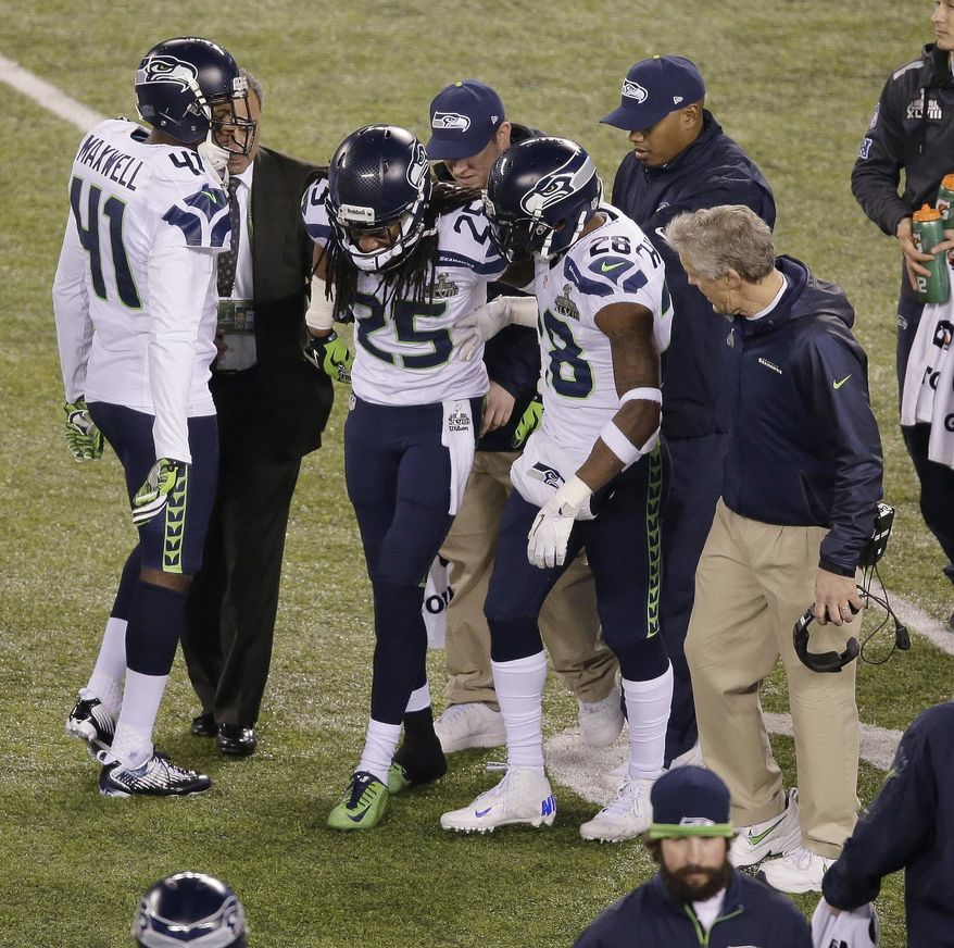 Seattle Seahawks' Richard Sherman (25) is helped off the field by Byron Maxwell (41) and Walter Thurmond (28) after he was injured on a play during the second half of the NFL Super Bowl XLVIII football game against the Denver Broncos Sunday, Feb. 2, 2014, in East Rutherford, N.J. (AP Photo/Charlie Riedel)
