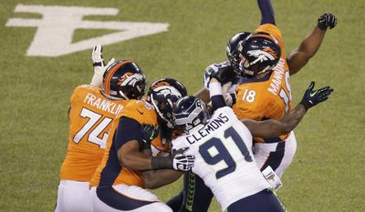 Denver Broncos' Peyton Manning is hit by Seattle Seahawks' Cliff Avril (56) and Seattle Seahawks' Chris Clemons (91) during the first half of the NFL Super Bowl XLVIII football game Sunday, Feb. 2, 2014, in East Rutherford, N.J. Manning was charged with an interception on the play. (AP Photo/Charlie Riedel)