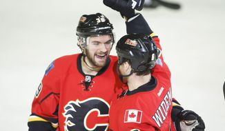 Calgary Flames' Dennis Wideman, right, celebrates his goal with teammate TJ Galiardi during second period of an NHL hockey game in Calgary, Alberta, Saturday, Feb. 1, 2014. (AP Photo/The Canadian Press, Jeff McIntosh)