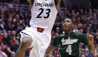 Cincinnati guard Sean Kilpatrick (23) drives past South Florida guard Corey Allen Jr. (4) in the first half of an NCAA college basketball game, Sunday, Feb. 2, 2014, in Cincinnati. (AP Photo/Al Behrman)